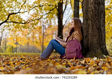 Girl sitting in the autumn park and thinkinig about her life with notes