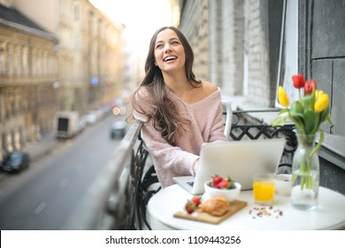 Girl sitting in the balcony, working with her laptop while having breakfast