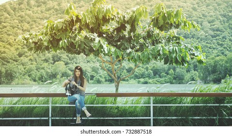 Girl sitting beside a river on a mountain background in holiday.