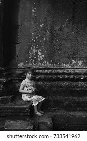 A girl sitting beside a wall at 14 July 2014, 12:54pm, Cambodia