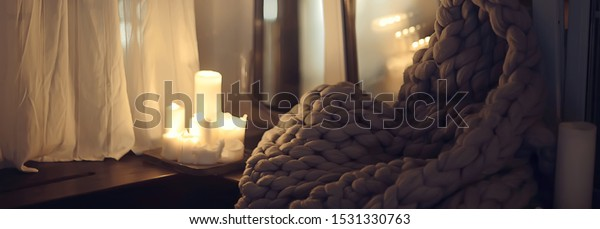 girl sitting in a blanket at the window, candles night, loneliness, young lonely girl, stress