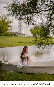 A girl is sitting in a boat near the lake
