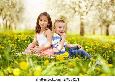 Girl sitting with boy in a blooming orchard