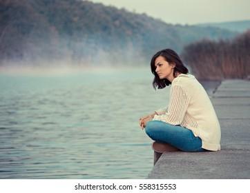 Girl  sitting by lake