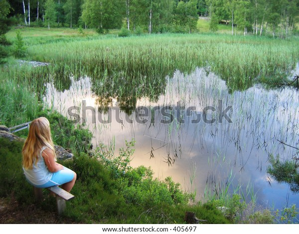 Girl sitting by lake reflecting the sky