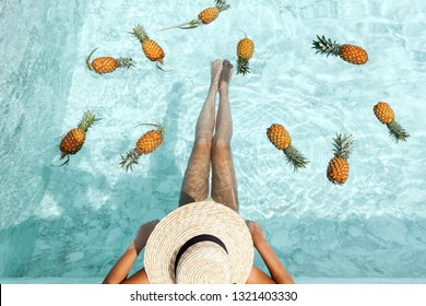 Girl sitting by pool with floating pineapples in blue clear water, photo of legs under hat closeup. Tropical fruit diet. Summer holiday idyllic concept top view.