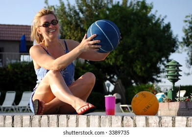 Girl Sitting By Swimming Pool Holding Basketball