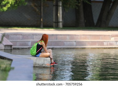 the girl is sitting by the water