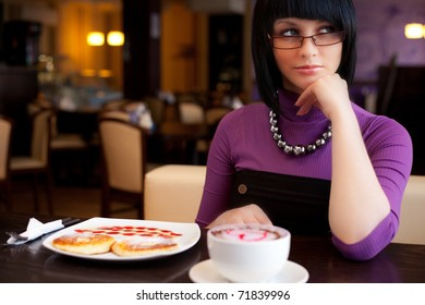 girl sitting in cafe with cup of coffee and food