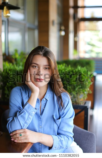 Girl sitting at cafe leaning on hand, wearing jeans shirt. Concept of having break and resting.