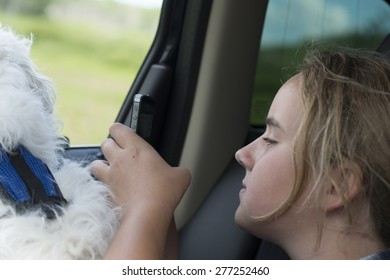 Girl sitting in a car using a mobile phone, Lake Audy Campground, Riding Mountain National Park, Manitoba, Canada