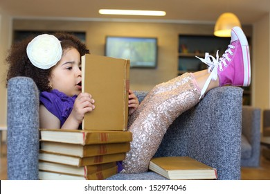girl sitting in a chair with a stack of books and reading