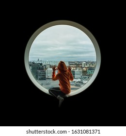 Girl sitting in a circular window longing or looking down on city below. View over Solna, Stockholm.