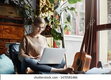 Girl sitting in cozy room near guitar and plants on armchair with crossed feet, holding laptop on laps and typing message, smiling broadly at camera, enjoying working under new design for customer