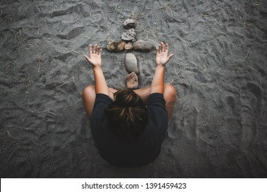 A girl sitting cross legged on a beach with her hands open, praising the stone cross before her.