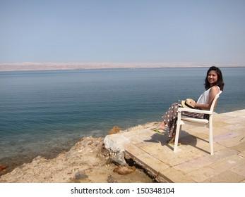 Girl sitting at Dead Sea, Jordan