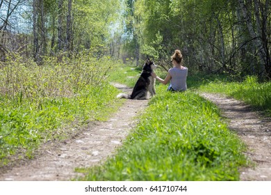 Girl sitting with dog in forest with beautiful view
