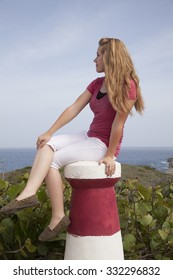 A girl sitting down on a pillar looking over her shoulder at the ocean.