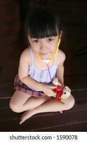 girl sitting down & testing stethoscope on toy dog