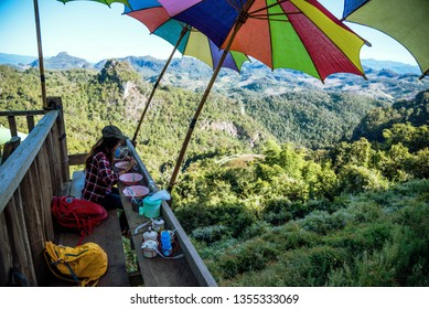 The girl sitting eating noodle in the rural village hanging legs style for viewpoint on the mountain,The local attractions of Mae Hong Son province Thailand.
