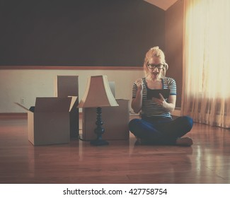 A girl is sitting in an empty room with boxes. She is holding a technology tablet for an interior design or moving concept.