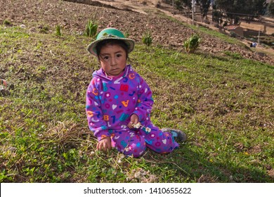 Girl sitting in the field with her mother. September 27, 2014 Huaraz, Peru.