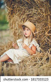 Fille assise dans un champ près d'une botte de foin avec un chapeau de paille