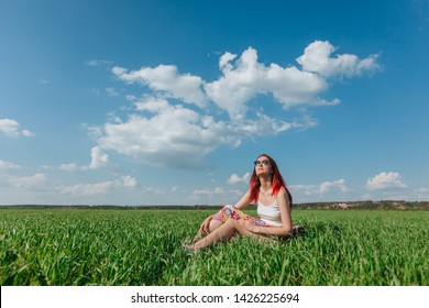 Girl sitting in a field on the green grass, blue sky background. Copy space