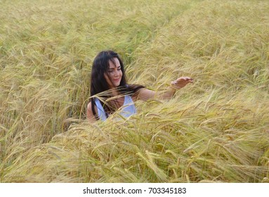 Girl sitting in the field and touching the spikelets of wheat