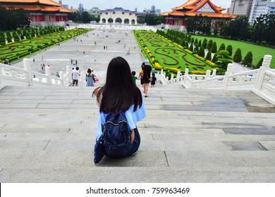 A girl sitting in front of Chiang Kai Shek Memorial Hall, Taipei, Taiwan