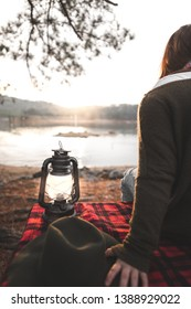 girl sitting in front of lake during sunset time and she has lamp.