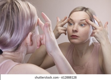 Girl sitting in front of a mirror. The girl looks in the mirror. Fear of aging, gerontology. Not want to grow old. 30. Skin problems, wrinkles, acne. Ugly woman.