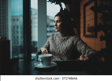 Girl sitting in front of a window, drinking coffy