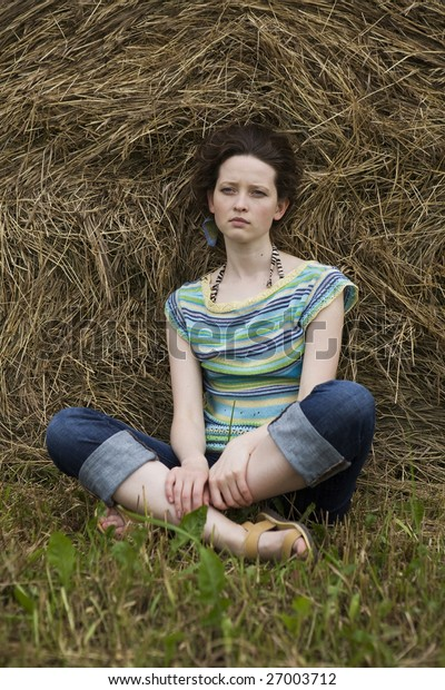 girl sitting at haystack