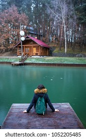 the girl is sitting with her back on a wooden bridge in a pine forest.