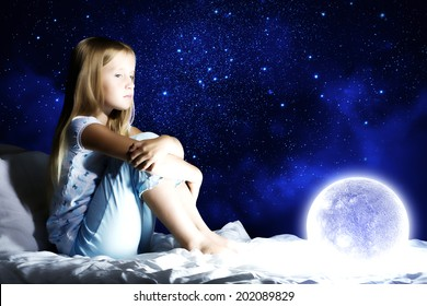 Girl sitting in her bed and dreaming
