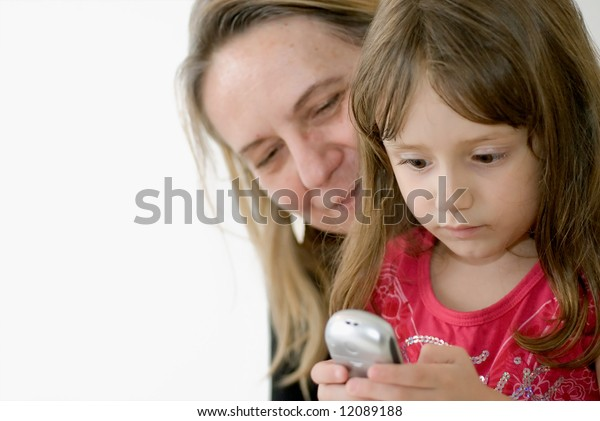 Girl sitting in her mother or grandmother's lap and learning how to use a cell phone