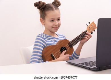 Girl sitting at home learns to play ukulele using online lessons.
