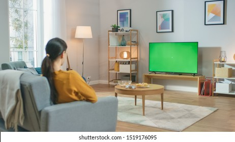 Girl Sitting At Home Sitting on a Couch, Watching Green Chroma Key Screen, Relaxing. Man in a Cozy Room Watching Sports Match, News, Sitcom TV Show or a Movie.
