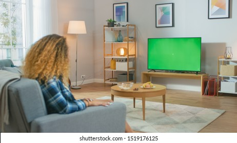Girl Sitting At Home Sitting on a Couch, Watching Green Chroma Key Screen, Relaxing. Man in a Cozy Room Watching Sports Match, News, TV Show or a Movie.