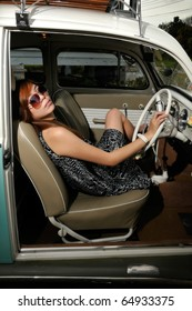 a girl sitting inside an antique car with sun glasses