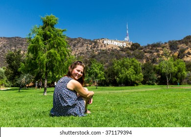 Girl sitting at in the Lake Hollywood Park and the Hollywood sign in the background in Los Angeles