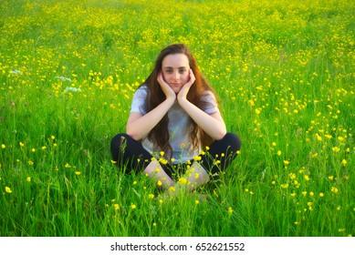 Girl sitting with legs crossed in field of wildflowers looking at camera