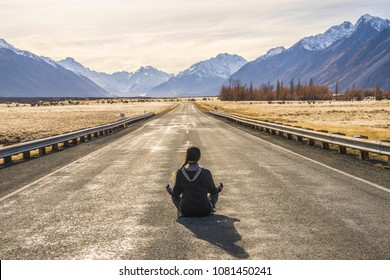 A girl sitting in the middle of an empty road in Mount Cook National Park, South Island, New Zealand.