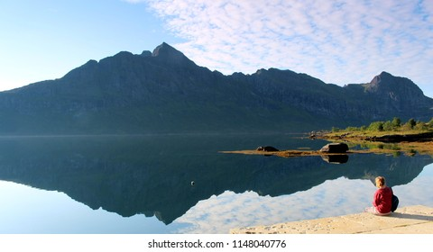 Girl sitting in the morning sunshine looking over a perfect reflection of a mountain in the Lofoten Islands, Norway