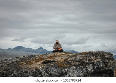 Girl sitting in nature on rock meditating/praying with beautiful mountain scenery in the background. Meditation, fitness, religious, lifestyle, yoga, sports, healthy living concept.