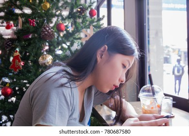 The girl sitting near by the window with Christmas tree background.