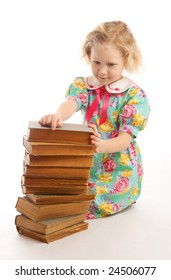 Girl sitting near old books stack