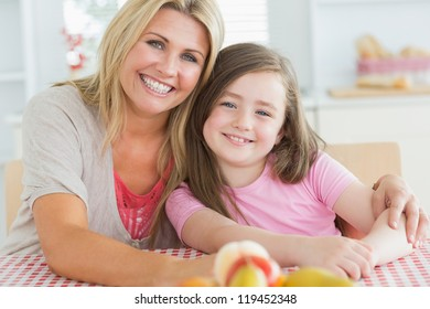 Girl sitting next to her mum at the kitchen embracing with fruit on the table