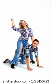 The girl is sitting on the back of her boyfriend and waving her hand like on a horse, they are fooling around and smiling, in plaid shirts
